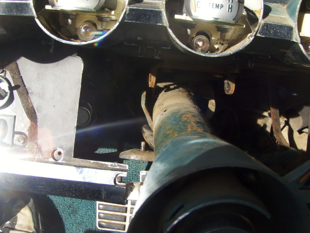 The column is attached under the dash to a U fitting with two bolts on either side.